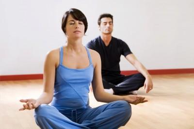 Una mujer y un hombre practican yoga