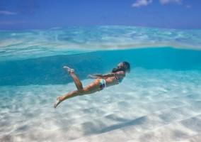 Mujer nadando en la playa