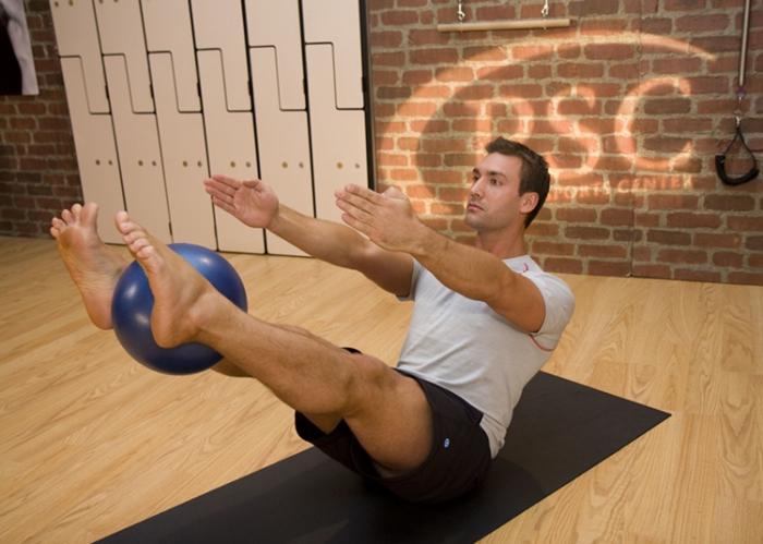 Hombre haciendo la V con pelota en Pilates