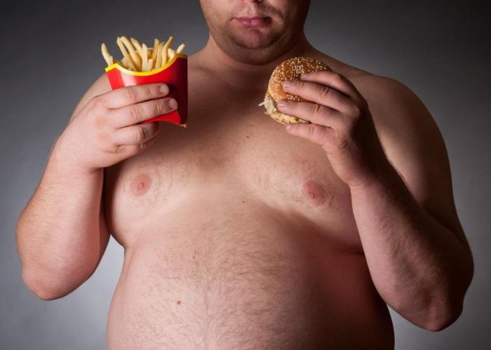 Hombre comiendo una hamburguesa con patatas fritas