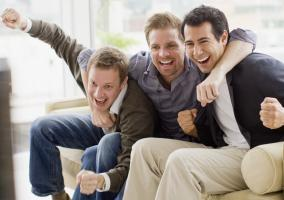 Amigos viendo un partido de fútbol en el salón de casa