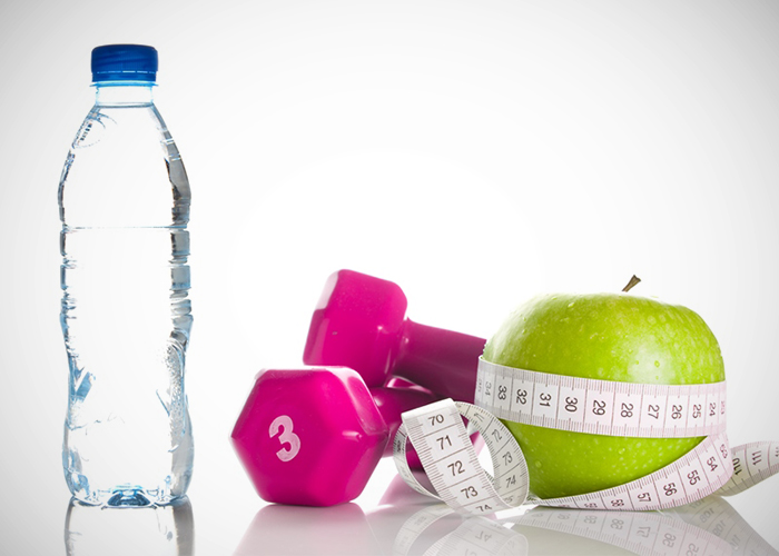Botella de agua, pesas, manzana y cinta métrica