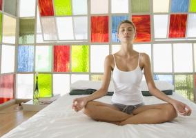 Joven chica haciendo Yoga en su cama