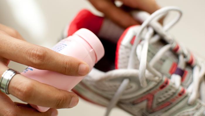 Echando desodorante para pies en el calzado