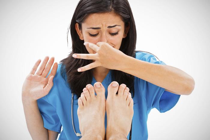 Médico oliendo pies