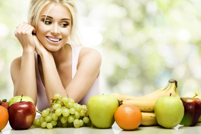 Chica joven delgada con verdura en la mesa