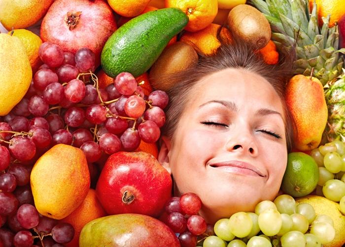 Mujer brotando entre frutas