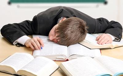 Trabajador durmiendo sobre libros