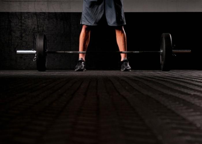 Hombre antes de levantar una barra con pesas