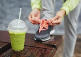 Zumo verde y corredor atándose las zapatillas