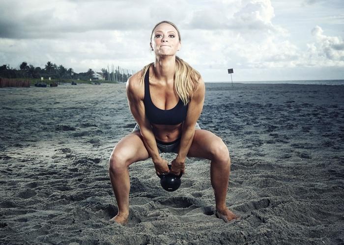 Mujer trabajando con kettlebell en la playa
