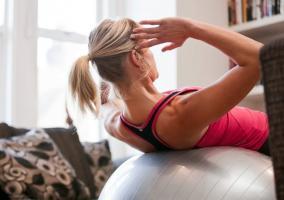 Mujer entrenando en el salón de casa