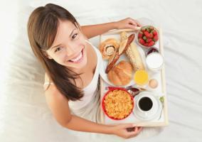 Mujer desayunando en la cama