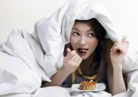 Chica comiendo en la cama a escondidas