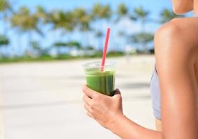 Mujer bebiendo zumo verde en la playa