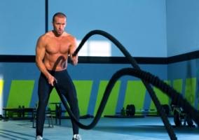 Hombre ejercitandose con cuerdas de batalla