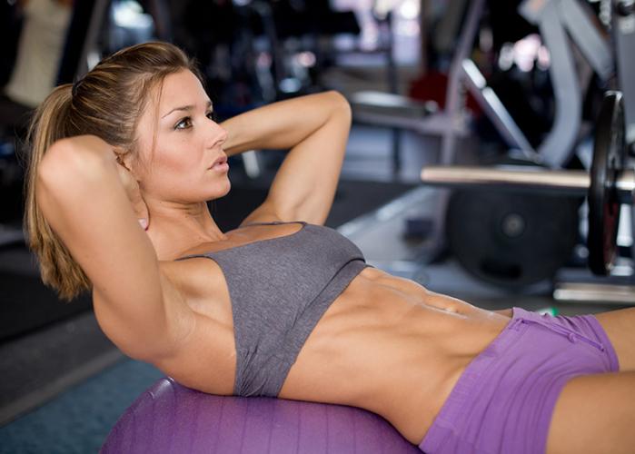Mujer haciendo abdominales sobre fitball