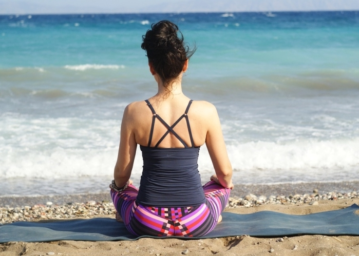 Mujer mirando el mar sentada en forma de Loto