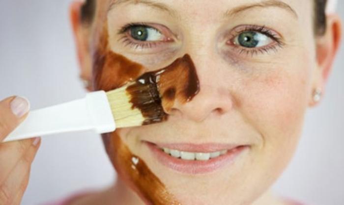 Mujer aplicando mascarilla de chocolate en el rostro