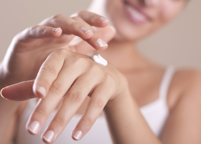 Mujer aplicándose crema en las manos