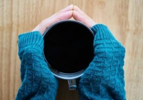 Mujer con frío sosteniendo taza de café