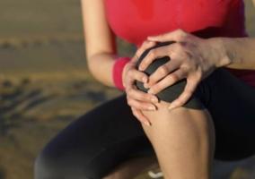 Mujer tocando rodillla