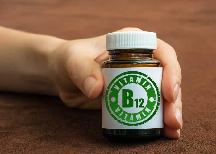 Mano con frasco vitamina B12
