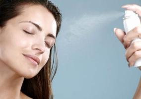 Mujer aplicando loción al rostro