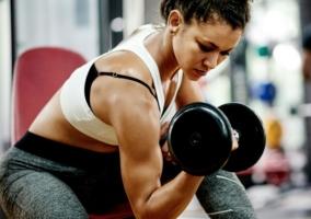 Mujer haciendo pesas en el gimnasio
