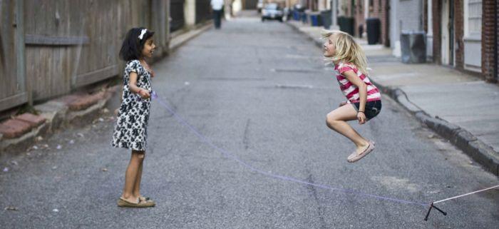 Pequeñas saltando a la comba en la calle